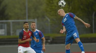 Pemain Islandia, Emil Hallfredsson (kanan) menghalau bola dari kejaran pemain Norwegia pada laga uji coba di Reykjavik, Islandia, (2/6/2018). Islandia kalah dari Norwegia 2-3. (AFP/Haraldur Gudjonsson)