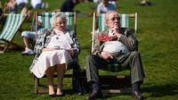 Sepasang lansia bersantai menikmati sinar matahari di atas kursi di Green Park, pusat kota London, Rabu (4/5). Awal Mei, suhu udara hangat mulai menyelimuti kota London. (Niklas HALLE'N/AFP)
