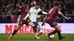 Gelandang Argentina, Lionel Messi, berusaha melewati bek Venezuela, Yordan Osorio, pada laga persahabatan di Stadion Wanda Metropolitano, Madrid, Jumat (22/3). Argentina kalah 1-3 dari Venezuela. (AFP/Philippe Marcou)