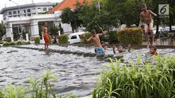 Anak-anak bermain di kolam air mancur penghias kawasan Pasar Baru, Jakarta, Selasa (29/1). Keterbatasan lahan bermain menyebabkan sebagian anak di Ibukota bermain tidak pada tempatnya, meskipun berbahaya bagi keselematan. (Liputan6.com/Immanuel Antonius)