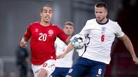 Pemain Denmark, Yussuf Poulsen, berebut bola dengan pemain Inggris, Eric Dier, pada laga UEFA Nations League di Stadion Parken, Rabu (9/9/2020). Kedua tim bermain imbang 0-0. (Liselotte Sabroe/Ritzau Scanpix via AP)