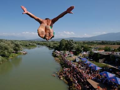 Penonton menyaksikan dari tepi sungai saat seorang peserta melakukan terjun bebas dari jembatan Ura e Shejnt dalam kompetisi menyelam tradisional ke-68 di Gjakova, Kosovo, 22 Juli 2018. Kompetisi ini dilakukan dari ketinggian 22 meter. (AP/Visar Kryeziu)
