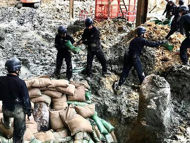 Polisi dari unit pejinak bom menempatkan karung pasir yang mengelilingi bom buatan AS yang dijatuhkan pada Perang Dunia II di persimpangan Convention Avenue dan Hung Hing Road di distrik Wan Chai di Hong Kong (11/5). (Handout / Polisi Hong Kong / AFP)