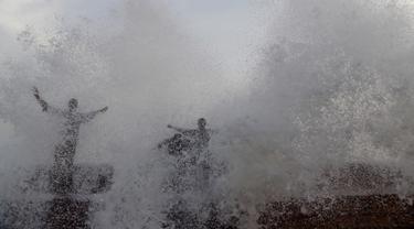 Orang-orang menikmati percikan air ombak selama musim panas di laut Arab di Karachi (14/6/2019). Memasuki musim panas, warga Pakistan ramai-ramai mendinginkan tubuhnya di laut. (AFP Photo/Asif Hassan)