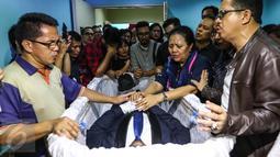 Kerabat dan keluarga berdoa di depan jenazah Mike Mohede di dalam peti di RS Bintaro Premiere, Tangsel, Minggu (31/7). Mike Mohede mengembuskan napas terakhirnya saat tidur siang di kamar seusai bermain game. (Liputan6.com/Fery Pradolo)