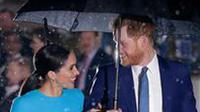 Pangeran Harry dan Meghan Markle sepayung berdua saat tiba di Endeavour Fund Awards, London, Inggris, Kamis (5/3/2020). Hujan lebat turun saat Pangeran Harry dan Meghan Markle tiba di lokasi. (AP Photo/Kirsty Wigglesworth)