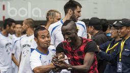 Kapten Persib Bandung, Atep, mengajak bercanda dengan mantan rekannya Makan Konate. Kehadiran pemain asal Mali itu ke Bandung untuk melepas kerinduan akan mantan klubnya Persib. (Bola.com/Vitalis Yogi Trisna)