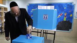 Pria Yahudi ultra-Ortodoks memberikan suaranya selama pemilihan parlemen Israel di Yerusalem (9/4). Warga Israel hari ini memberikan suara dalam pemilihan tingkat tinggi yang akan memutuskan masa jabatan PM Benjamin Netanyahu meskipun ada dugaan korupsi yang dilakukannya. (AFP Photo/Menahem Kahana)