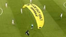 "Di parasut kuning ciri khas Greenpeace saat melakukan aksi tertulis ""Kick Out Oil! Greenpeace"". (Foto: AP/Pool/Alexander Hassenstein)"