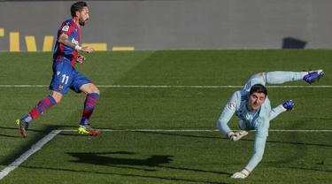 Pemain Levante Jose Luis Morales (kiri) mencetak gol ke gawang Real Madrid yang dijaga Thibaut Courtois pada pertandingan Liga Spanyol di Stadion Alfredo Di Stefano, Madrid, Spanyol, Sabtu (30/1/2021). Real Madrid kalah 1-2. (AP Photo/Manu Fernandez)