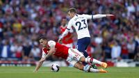 Gelandang Arsenal, Granit Xhaka, terjatuh saat berebut bola dengan gelandang Tottenham Hotspur, Christian Eriksen, pada laga Premier League 2019 di Stadion Emirates, Minggu (1/9). Kedua tim bermain imbang 2-2. (AP/Alastair Grant)