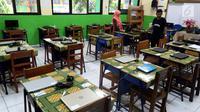 Petugas mengecek kesiapan laptop dan ruang untuk Ujian Nasional Berbasis Komputer di SMP N 34 Pademangan, Jakarta Utara, Minggu (22/4). UNBK SMP 2018 akan berlangsung mulai besok Senin (23/4). (Liputan6.com/Johan Tallo)