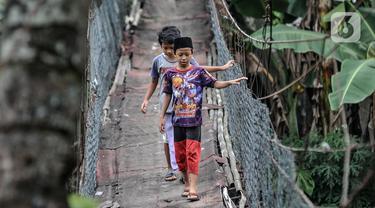Anak-anak melintasi jembatan gantung yang sudah tidak layak di kawasan Srengseng Sawah, Jakarta, Sabtu (12/6/2021). Jembatan gantung di atas Sungai Ciliwung tersebut saat ini dalam kondisi tidak layak dan dapat membahayakan keselamatan warga yang melintas. (merdeka.com/Iqbal S. Nugroho)