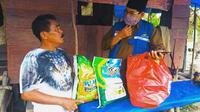 Masyarakat terdampak covid-19 ketika menerima bantuan dalam bentuk sembako. (Liputan6.com/M Syukur)