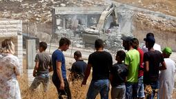 Warga Palestina menyaksikan pasukan Israel menghancurkan bangunan palestina di Yerusalem (22/7/2019).Penghancuran terkait putusan pengadilan tinggi Israel pada Juni 2019 lalu yang menolak petisi warga Palestina yang meminta pembatalan perintah militer melarang konstruksi. (AFP Photo/Ahmad Gharabli)