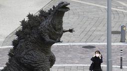 Seorang wanita menyesuaikan masker wajahnya saat berjalan dekat patung Godzilla di Tokyo, Jepang, Jumat (16/10/2020). Ibu Kota Jepang itu mengonfirmasi lebih dari 180 kasus virus corona COVID-19 baru pada hari Jumat. (AP Photo/Hiro Komae)