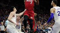 Pemain Miami Heat, Dwyane Wade melakukan tembakan melewati adangan para pemain Philadelphia 76ers pada NBA basketball playoff series di Wells Fargo Center, Philadelphia, (16/4/2018). Heat menang 113-103. (AP/Chris Szagola)