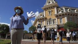 Pegawai yang mengenakan masker untuk mencegah penyebaran COVID-19 menyambut pengunjung di Disneyland Hong Kong, Kamis (18/6/2020). Disneyland Hong Kong kembali beroperasi pada 18 Juni 2020 dengan menerapkan sejumlah protokol kesehatan baru. (AP Photo/Kin Cheung)