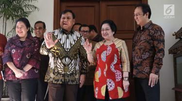 Ketua Umum Partai Gerindra Parbowo Subianto (dua kiri) dan Ketua Umum PDIP Megawati Soekarnoputri (dua kanan) melambaikan tangan jelang menggelar pertemuan di kediaman Megawati, Jalan Teuku Umar, Jakarta, Rabu (24/7/2019). Prabowo dan Megawati kompak memakai batik. (Liputan6.com/Helmi Fithriansyah)