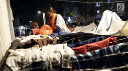 Pencari suaka menjemur pakaian di luar tenda yang dibangun di atas trotoar depan kantor UNHCR, Jalan Kebon Sirih, Jakarta, Jumat (5/7/2019). Para pencari suaka dari sejumlah negara berkonflik berharap UNHCR bisa segera memberikan jaminan perlindungan bagi mereka. (Liputan6.com/Helmi Fithriansyah)
