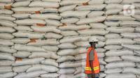 Pekerja berjalan di dekat susunan karung berisi beras di Gudang Bulog Divisi Regional DKI Jakarta, Kelapa Gading, Kamis (18/3/2021). Adapun dari total pengadaan sebanyak 1.785.450 ton beras, tersisa 275.811 ton beras belum tersalurkan. (merdeka.com/Iqbal S Nugroho)