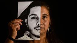 Gladys Betancourth, 51, ibu dari Oscar Obando, 24, satu dari 8 pemuda yang dibunuh dalam pesta di pinggiran Samaniego, Kolombia pada 16 Agustus, berpose dengan foto putranya pada 2 September 2020. Pembunuhan kembali berdarah di pedesaan Kolombia. Korbannya kebanyakan masih muda. (Luis ROBAYO/AFP)