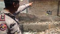 Kapolsek Tamalate, Kompol A. Arifuddin tampak menunjuk bagian tembokpembatas yang runtuh dan menimpa dua bocah bersaudara di Makassar hingga tewas (Liputan6.com/ Eka Hakim)