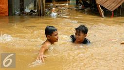 Anak-anak bermain di lokasi banjir yang merendam kawasan Kampung Pulo, Jakarta, Rabu (25/11). Air aliran kali Ciliwung mulai memasuki rumah warga sekitar pukul 03.00 Wib dini hari tadi. (Liputan6.com/Yoppy Renato)