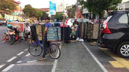 PKL menutup sebagian badan trotoar di kawasan Jatinegara, Jakarta, Senin (24/9). Kondisi trotoar yang telah diperlebar Pemprov DKI Jakarta kini dipenuhi PKL dan parkir liar sehingga mengganggu kenyamanan pejalan kaki. (Liputan6.com/Immanuel Antonius)