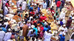 Pedagang kaki lima Bangladesh menjajakan makanan untuk berbuka puasa di pasar tradisional di Dhaka pada 10 Mei 2019. Seperti jutaan muslim di seluruh dunia, muslim Bangladesh berpuasa setiap hari selama bulan Ramadan dengan tidak makan dan minum dari subuh hingga petang. (MUNIR UZ ZAMAN/AFP)