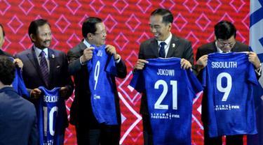 Presiden Joko Widodo menunjukkan jersey pada acara penandatanganan Nota Kesepahaman antara FIFA dan ASEAN di Bangkok, Sabtu (2/11/2019). Jokowi mendapat nomor punggung 21 karena keberhasilan Indonesia ditunjuk sebagai tuan rumah Piala Dunia U-20 pada 2021 mendatang. (Liputan6.com/Biro Pers Setpres)