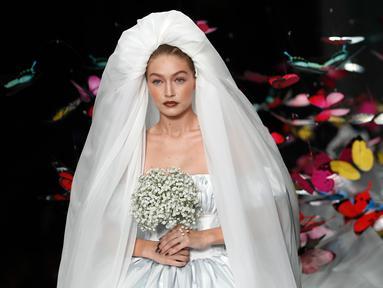 Supermodel Gigi Hadid berjalan di runway mengenakan gaun rumah mode Moschino untuk koleksi SS19 selama gelaran fashion week di Milan, Italia, Kamis (20/9). Gigi Hadid mencuri perhatian publik dengan tampil bak seorang pengantin. (AP/Antonio Calanni)