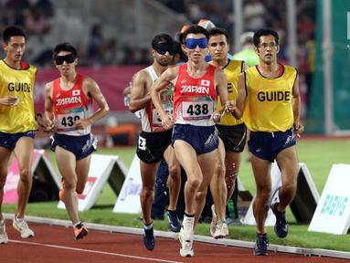 Pelari 5000 meter putra kategori T11 Asian Para Games 2018 saat laga final di SUGBK, Jakarta, Jumat (12/10). T11 adalah klasifikasi pelari disabilitas netra, karenanya dalam setiap lomba didampingi pemandu atau guide. (Liputan6.com/Helmi Fithriansyah)
