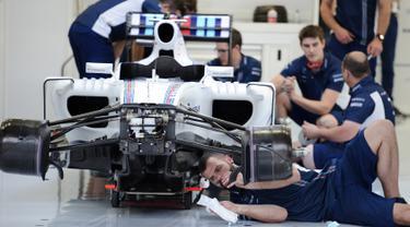 Tim Williams Martini Racing merakit mobil Formula 1 di Sirkuit Sakhir, Bahrain (31/3). jelang Grand Prix F1 Bahrain, Sejumlah tim sibuk mempersiapkan mobil terbaiknya masing-masing. (AFP PHOTO/MOHAMMED AL-SHAIKH)