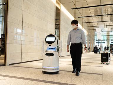 """Seorang staf mencoba menggunakan sebuah robot pemandu dalam uji coba yang dilakukan di sebuah bangunan komersial di Tokyo, Jepang (14/9/2020). Acara tersebut, sebagai bagian dari proyek """"Tokyo Robot Collection"""" yang diprakarsai pemerintah kota metropolitan Tokyo. (Xinhua/Pemerintah Kota Metropolitan"""