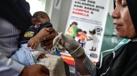 Petugas menyuntikan Vaksin Campak dan Rubella (MR) kepada bayi saat dilakukan imunisasi di sebuah puskesmas, Banda Aceh, Rabu (19/9). Pemerintah Aceh memperbolehkan penggunaan vaksin MR dengan alasan dalam kondisi darurat. (CHAIDEER MAHYUDDIN / AFP)