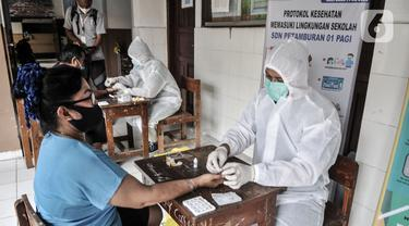 Tim medis dari Polda Metro Jaya saat menggelar rapid test kepada warga di SDN 01 Petamburan, Jakarta, Minggu (22/11/2020). Polda Metro Jaya menggelar rapid test gratis kepada warga Petamburan sebagai langkah mencegah penyebaran Covid-19. (merdeka.com/Iqbal S. Nugroho)