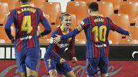 Penyerang Barcelona, Antoine Griezmann, melakukan selebrasi bersama Lionel Messi  usai mencetak gol ke gawang Valencia pada laga Liga Spanyol di Stadion Mestalla, Minggu (2/5/2021). Barcelona menang dengan skor 2-3.  (AP Photo/Alberto Saiz)