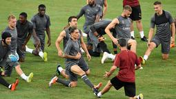 Para pemain Arsenal melakukan pemanasan saat mengikuti sesi latihan tim di Singapura (27/7). Arsenal akan bertanding melawan PSG pada International Champions Cup 28 Juli. (AFP Photo/Roslan Rahman)