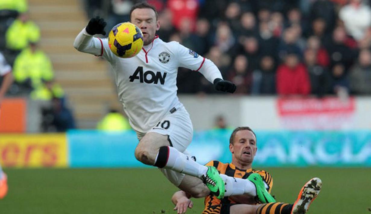 Pemain Hull City terpaksa harus melakukan pelanggaran untuk menghentikan laju penyerang Manchester United, Wayne Rooney dalam laga lanjutan Liga Premier di KC Stadium, Kamis (26/12/2013) malam WIB.(AFP/Lindsey Parnaby)