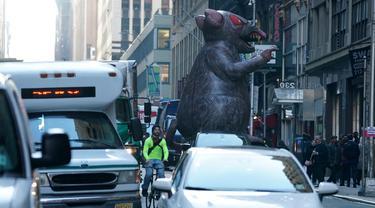 Balon tikus raksasa berjalan di tengah kota untuk diletakkan di luar kantor perusahaan sebagai simbol protes di New York, Kamis (26/12/2019). Serikat pekerja Amerika telah menggunakan balon tikus  untuk menyoroti praktik perburuhan yang tidak adil sejak 1990-an. (TIMOTHY A. CLARY/AFP)