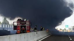 Petugas pemadam kebakaran berada di lokasi ledakan truk tangki yang membawa bahan mudah terbakar di jalan raya dekat kota Bologna, Italia, Senin (6/8). Kuatnya ledakan bahkan sampai menyebabkan jalan layang rusak. (AFP/Gianni SCHICCHI)