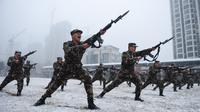 Polisi militer saat mengikuti sesi pelatihan menggunakan senapan berpisau di tengah hujan salju di Hefei, China (15/1/2020). Latihan fisik yang dilakukan anggota polisi militer China meliput angkat ban traktor hingga teknik menyerang dengan menggunakan senapan berpisau. (AFP Photo/Str/China Out)