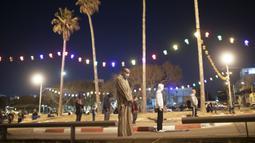 Umat muslim menerapkan jaga jarak aman saat melaksanakan salat tarawih di sebuah tempat parkir di kota campuran Yahudi-Arab, Jaffa, Israel, Minggu (10/5/2020). Israel menutup tempat umum dan rumah ibadah untuk mencegah penyebaran virus corona COVID-19. (AP Photo/Oded Balilty)