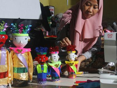 Perajin menyelesaikan pembuatan miniatur ondel-ondel di rumah produksi Kramat Jati, Jakarta, Senin (23/6/2019). Miniatur ondel-ondel yang terbuat dari limbah botol plastik itu dibuat sesuai dengan pesanan. (merdeka.com/Arie Basuki)