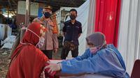 Kapolsek Sawangan, AKP Muhammad Melta Mubarak meninjau vaksinasi Covid-19 di kawasan kumuh, Kecamatan Bojongsari, Kota Depok. (Liputan6.com/Dicky Agung Prihanto)
