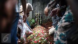 Para kerabat berdoa disamping makam alm Guntoro di Lenteng Agung, Jakarta, Kamis (16/2). Diduga terkena serangan jantung , Guntoro, wartawan foto, Koran Jakarta meninggal dunia saat meliput banjir di daerah Pejaten Timur. (Liputan6.com/Faizal Fanani)