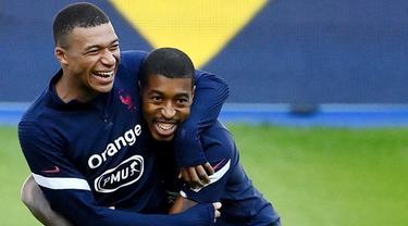 Penyerang Prancis, Kylian Mbappe, bercanda dengan Presnel Kimpembe, saat sesi latihan jelang laga UEFA Nations League di Paris, Senin (7/9/2020). Pemain muda PSG itu akan absen melawan Kroasia karena dinyatakan positif terjangkit COVID-19. (AFP/Franck Fife)