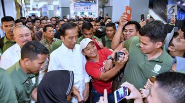 Seorang remaja berswafoto dengan Presiden Joko Widodo atau Jokowi saat menyambangi Palembang Square, Palembang (21/1). Banyak warga terkejut mengetahui kedatangan Presiden di sebuah mal Palembang tersebut. (Liputan6.com/Pool/Biro Setpres)