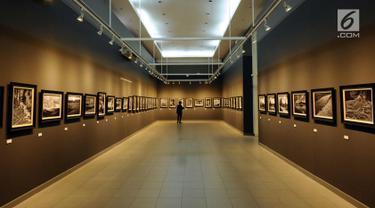 Pengunjung menikmati deretan foto bertema Melampaui Fotografi karya Suherry Arno di Galeri Nasional, Jakarta, Selasa (24/10). Pameran foto tunggal karya Suherry Arno ini berlangsung hingga 5 November 2017. (Liputan6.com/Helmi Fithriansyah)